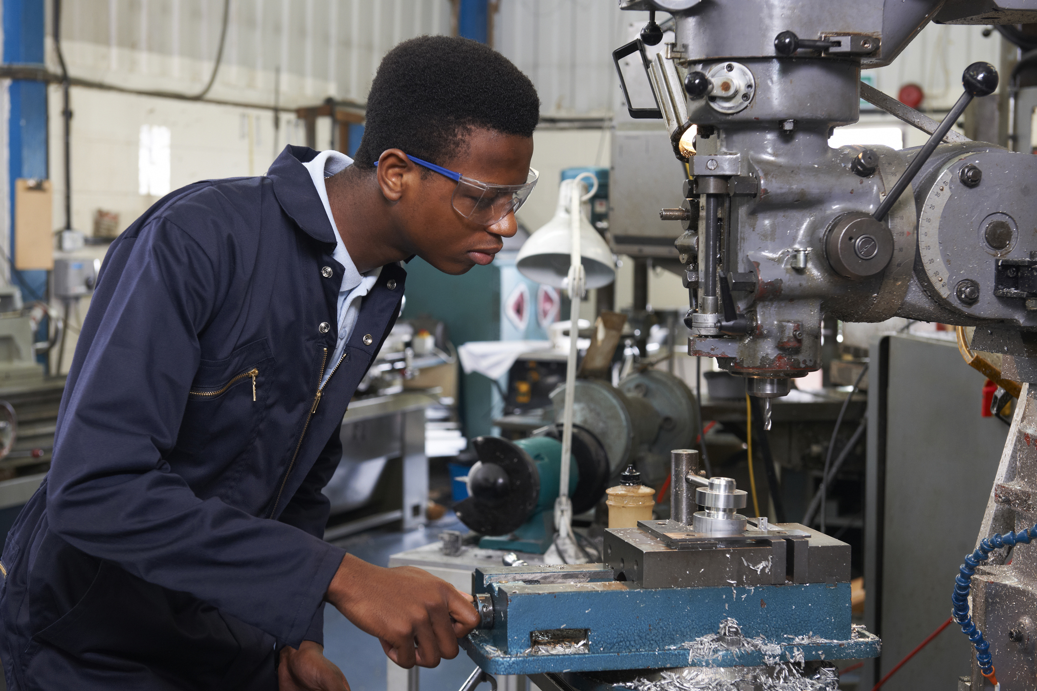 Photograph of Male Apprentice Engineer Working On Drill In Factory